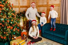 Happy family of four in knitted sweaters for Christmas royalty free stock photos