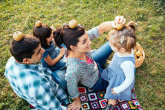 Happy family of four lying in the grass playing with apples in a Royalty Free Stock Images