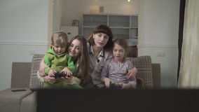 Happy family of four members play the video game. Two small kids hold joysticks. Fun family holiday. stock video