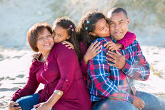 Happy family of four outdoors. Sitting with children kissing parents on the cheeks stock images