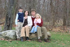 Happy Family of Four People (1)b. Family of four on rocks in wooded yard in winter season. (Horizontal Stock Photo