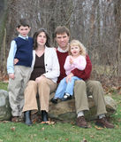Happy Family of Four People (1) Portrait. Family of four on rocks in wooded yard in winter season. (Vertical Stock Photos