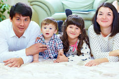Happy family of four persons at home Stock Photo