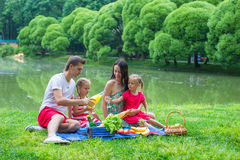 Happy family of four picnicking in the park on Stock Photos