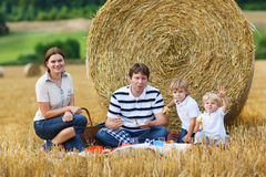 Happy family of four picnicking on yellow hay field in summer. Stock Photography