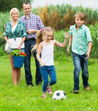 Happy family of four playing football Royalty Free Stock Photography