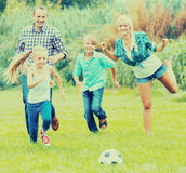 Happy family of four playing football Royalty Free Stock Photo