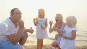 Happy family of four Playing wit Soap Bubbles outdoor on the beach during beautiful sunset happy vacation time in slow