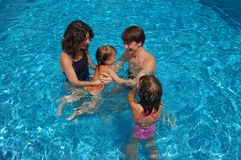 Happy family of four in the pool Royalty Free Stock Images