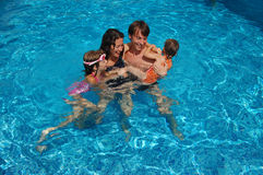 Happy family of four in the pool Stock Images