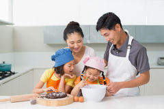 Happy family of four preparing cookies in kitchen Stock Image