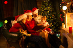 Happy family of four reading together on Christmas evening Royalty Free Stock Photography