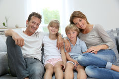 Happy family of four relaxing on sofa Stock Image
