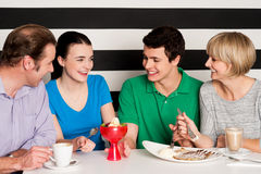 Happy family of four in restaurant. Cheerful family of four relishing delicious eatables and dessert royalty free stock image