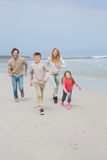 Happy family of four running at beach Royalty Free Stock Images