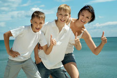 Happy family of four showing thumbs up Stock Image
