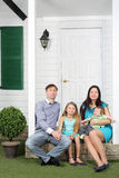Happy family of four sit on porch of new their cottage. stock photography
