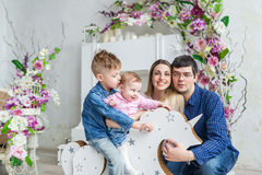 Happy family of four sit in room with flowers and play with kids on her wooden toy horse Royalty Free Stock Image
