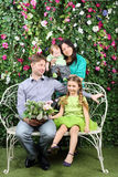 Happy family of four sit on white bench with bunch of flowers Stock Photography