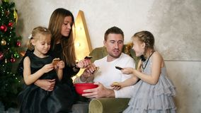 Happy family of four sitting by the Christmas tree and eating chocolate cookies. Cute mother, father and two daughters. Celebrating Christmas together stock footage