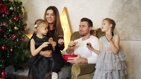 Happy family of four sitting by the Christmas tree and eating chocolate cookies. Cute mother, father and two daughters. Celebrating Christmas together stock video