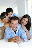 Happy family of four sitting at home having fun Stock Images