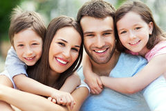 Happy family of four. Happy family smiling together outdoors Stock Photos