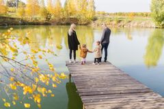 Happy family of four stand on the wooden pier in warm autumn day. Back view royalty free stock images