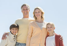 Happy Family Of Four Standing Against Clear Blue Sky Royalty Free Stock Image