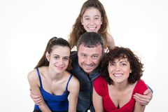 Happy family of four standing indoors with father mother and two daughter royalty free stock photography