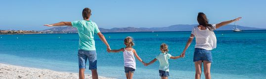 Happy family of four during summer beach vacation stock images