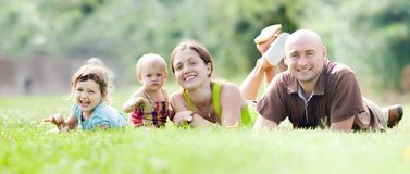 Happy family of four in summer park royalty free stock photo