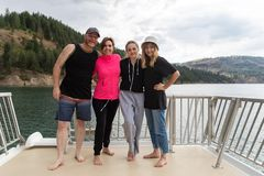 Happy family of four together on lake vacation royalty free stock photography