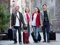 Happy family of four with trunks and bags Stock Photography
