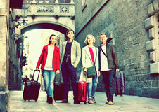 Happy family of four with trunks and bags Royalty Free Stock Photos