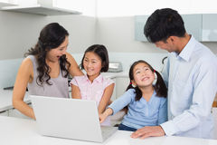 Happy family of four using laptop in kitchen. Happy family of four using laptop in the kitchen at home Stock Photography