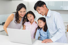 Happy family of four using laptop in kitchen. Happy family of four using laptop in the kitchen at home Royalty Free Stock Image