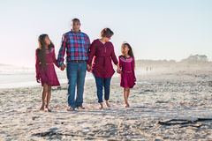 Happy family of four walking on the beach interacting. Happy family of four walking on the beach barefoot, interacting. Full length with people talking and stock photography