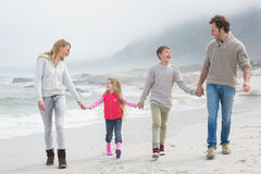 Happy family of four walking hand in hand at beach Stock Photos