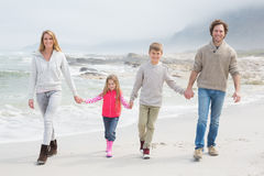 Happy family of four walking hand in hand at beach Royalty Free Stock Photo