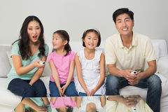 Happy family of four watching tv in living room. Portrait of a happy family of four watching tv in the living room at home royalty free stock photo