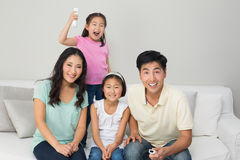 Happy family of four watching tv in living room Royalty Free Stock Photography