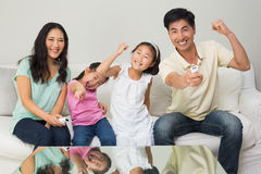 Happy family of four watching tv in living room. Portrait of a happy family of four watching tv in the living room at home stock photography