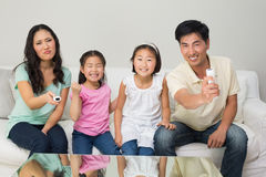 Happy family of four watching tv in living room. Portrait of a happy family of four watching tv in the living room at home stock images