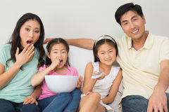 Happy family of four watching tv in living room. Portrait of a happy family of four watching tv in the living room at home royalty free stock photography