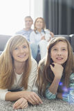 Happy family of four watching TV together at home Stock Photos