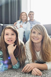 Happy family of four watching TV together at home Stock Photography