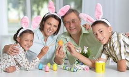 Happy family of four wearing bunny ears and painting Easter eggs Royalty Free Stock Photo