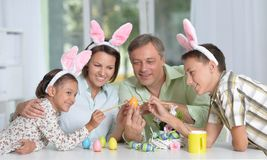 Happy family of four wearing bunny ears and painting Easter eggs. At home Stock Images