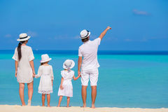 Happy family of four on white beach vacation Stock Image